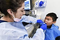 In the new Healthy Smiles Van, a dentist looks at a Mayfair Elementary student's teeth